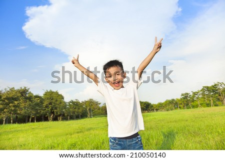 happy children standing on meadow and raise hands  - stock photo