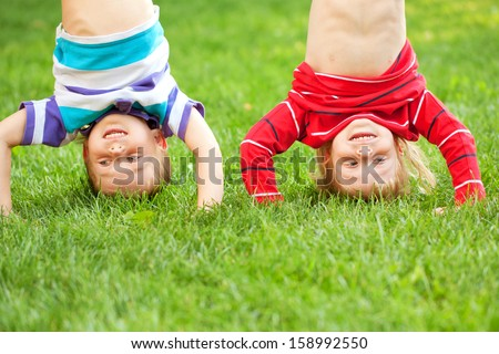 Happy children standing upside down on the grass in an urban neighborhood. Fun kid's holiday. - stock photo