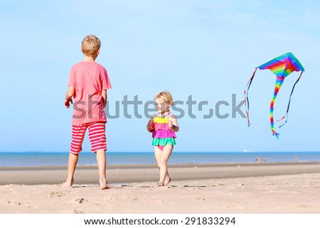 Happy children, teenager brother with cute toddler sister, playing together on the beach flying colorful kite - stock photo