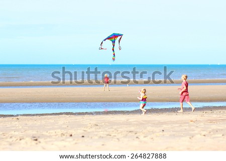 Happy children, teenager brothers with cute toddler sister, playing together on the beach flying colorful kite - stock photo