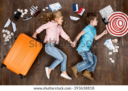Happy children. Top view creative photo of little boy and girl on vintage brown wooden floor. Children lying near travel things. Girl with suitcase - stock photo
