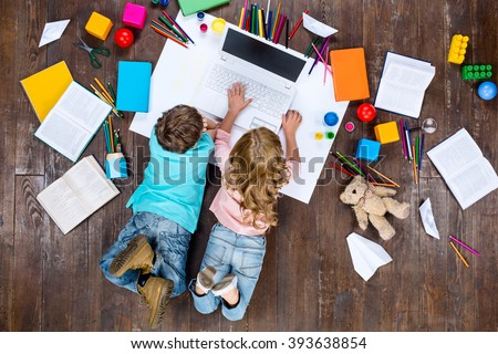 Happy children. Top view creative photo of little boy and girl on vintage brown wooden floor. Children lying near books and toys, and using laptop - stock photo