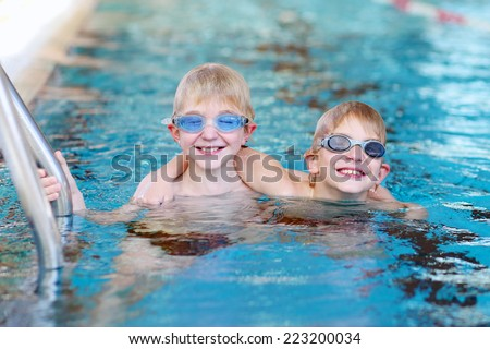 Happy children, twin teenagers boys in swimming goggles, having fun in the pool training before competition - stock photo