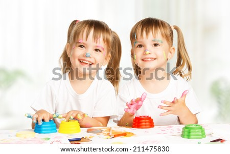 happy children twins girl draws paints , get dirty - stock photo