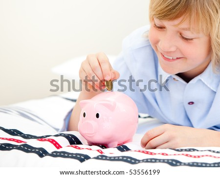 Happy children using a piggy bank at home - stock photo