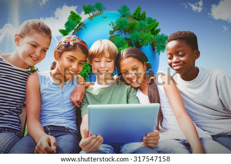 Happy children using digital tablet at park against blue sky over green field