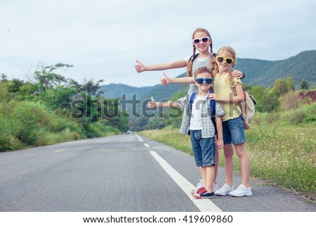 Happy children  walking on the road at the day time.  Concept of friendly family. - stock photo