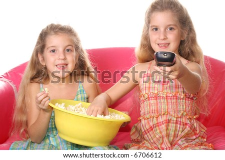 happy children watching a movie eating popcorn - stock photo