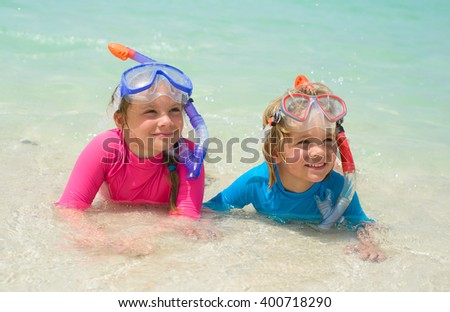 Happy children wearing snorkeling gear  on the beach - stock photo