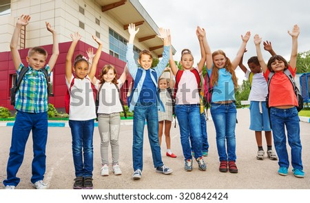 Happy children with arms up standing near school - stock photo