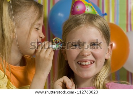 Happy children with birthdaywhistle on a striped background