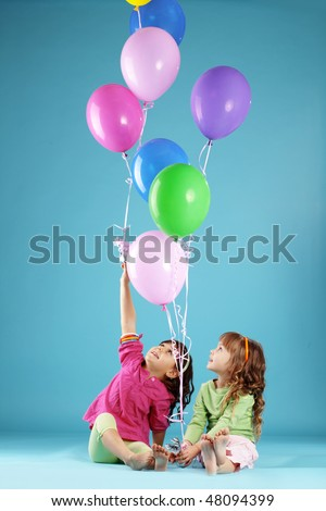 Happy children with colorful air ballons over blue - stock photo