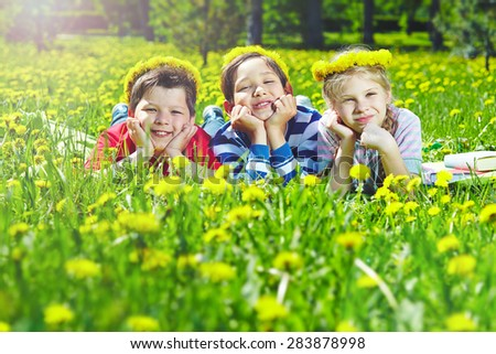 Happy children with dandelion wreaths having rest in natural environment  - stock photo