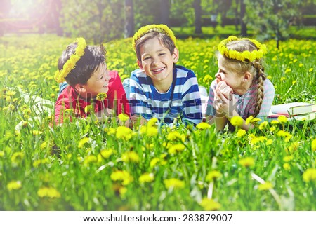 Happy children with dandelion wreaths relaxing on lawn in park
