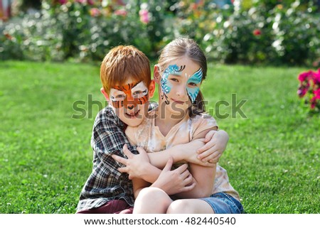 Happy children with face art paint in park. Boy and girl outdoors on child birthday masquerade party have fun, smile and hug each other as friends or siblings. Entertainment and holidays.