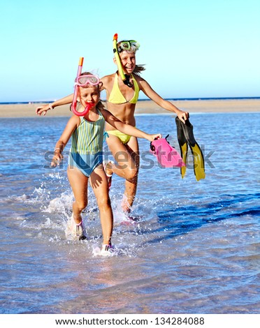 Happy children with flippers running on  beach. - stock photo