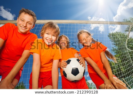 Happy children with football view from below - stock photo