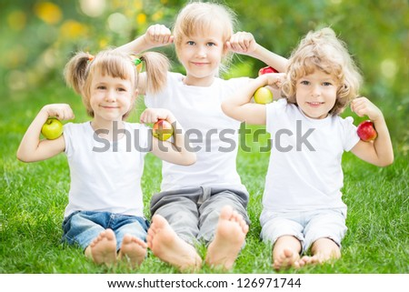 Happy children with fruits sitting on green grass in spring park - stock photo