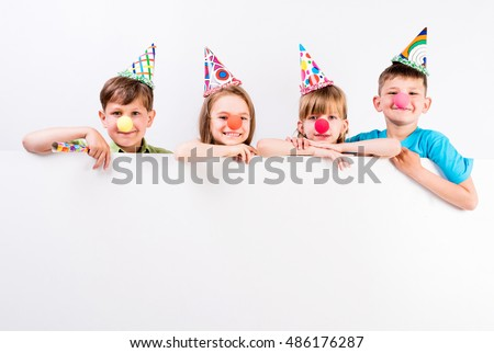 happy children with holiday decorations and advertisement blank in front of them