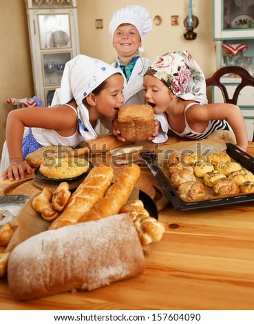 Happy children with table full of  homemade pastry - stock photo