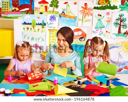 Happy children  with teacher at classroom. - stock photo