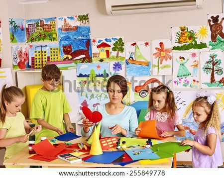 Happy children  with teacher at classroom. In background kids pictures - stock photo