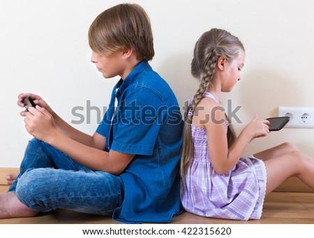 Happy childrenen enjoying  modern smartphones indoors - stock photo