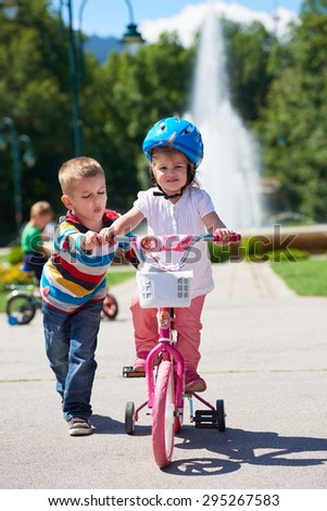 Happy childrens outdoor,  brother and sister in park have fun. Boy and girl in park learning to ride a bike.
