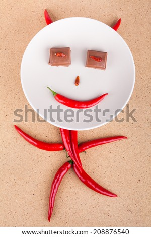 Happy chili pepper character with chocolate eyes on plate, over wooden background. - stock photo