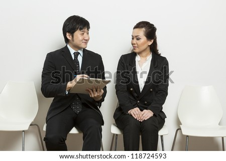 Happy Chinese business man interviewing female applicant.
