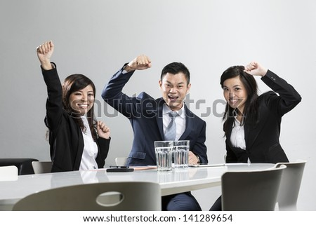 Happy Chinese business people cheering in a meeting. Concept about success and achivement. - stock photo