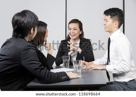 Happy Chinese Business team having a meeting in the office. - stock photo