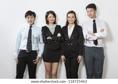 Happy Chinese business team standing in a row and leaning against a wall.