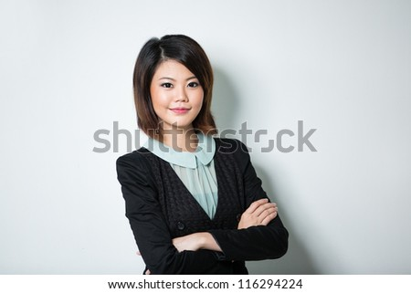 Happy Chinese business woman leaning against a wall. - stock photo