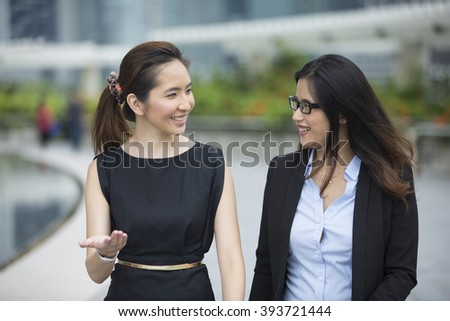 Happy Chinese Business women walking outside office & talking to each other.