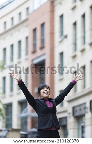 Happy Chinese businesswoman with arms raised. Concept about a freedom and achievement.