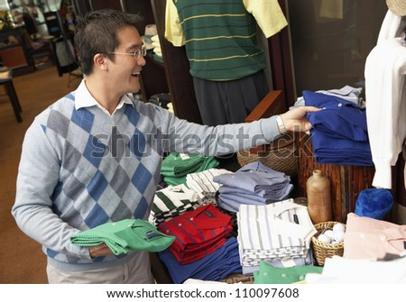 Happy Chinese man buying shirts in clothing store - stock photo