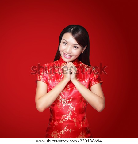 happy Chinese new year. Asian woman with gesture of congratulation isolated on red background - stock photo