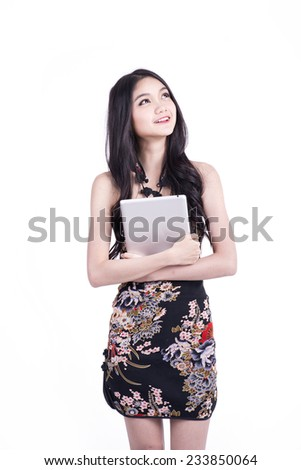 happy Chinese new year. beautiful young Asian woman holding tablet pc with empty screen - stock photo