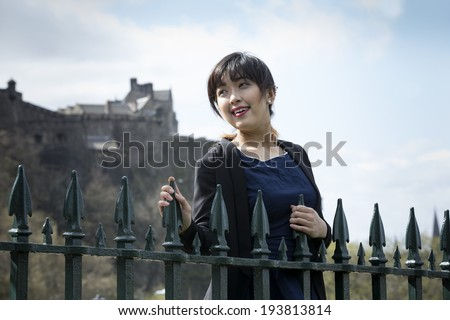 Happy Chinese tourist in Edinburgh, UK. Beautiful young Asian woman on vacation  - stock photo