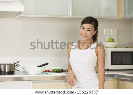 Happy Chinese woman standing at home in her kitchen