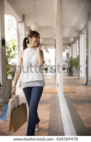 Happy Chinese woman using a smartphone and holding shopping bags.  - stock photo