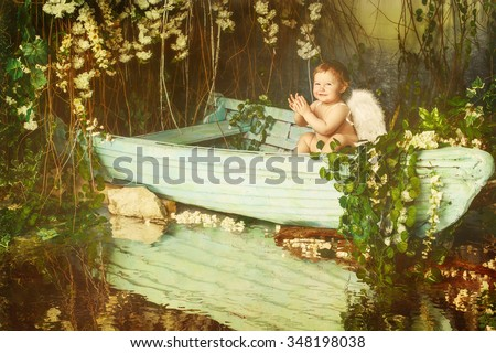 Happy Christmas Baby Angel with Wings sitting on boat in green bush - stock photo