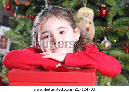 Happy Christmas child resting her hand on present in front of Christmas tree - stock photo