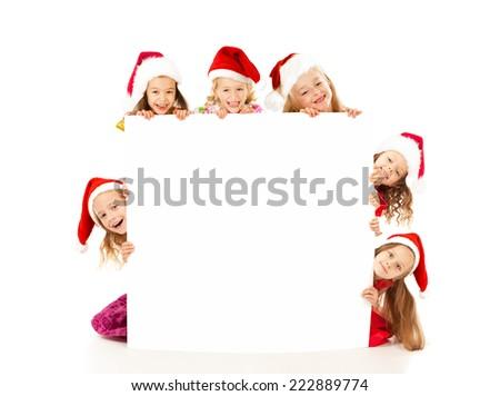 Happy Christmas children  in santa hats holding white blank - stock photo