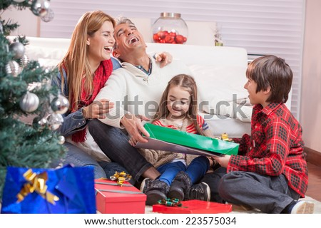 Happy Christmas family at home unwrapping presents. - stock photo