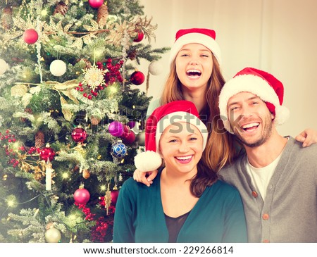 Happy Christmas Family portrait. Smiling Parents with teenage daughter at Home Celebrating New Year. Christmas Tree.  - stock photo