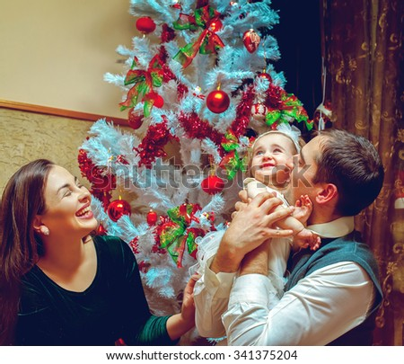 Happy christmas family with little baby girl. Parents smiling and having fun with child. Christmas mood. New year. - stock photo