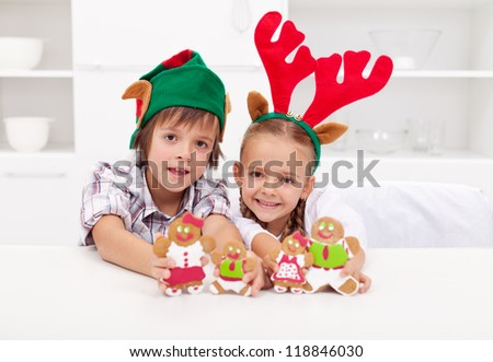 Happy christmas kids with elf and reindeer hats holding decorated gingerbread people