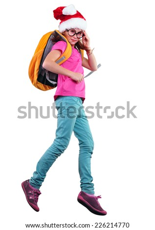 happy Christmas schoolgirl with Santa red hat with a backpack exercising, running and jumping. Isolated over white background. Education childhood concept - stock photo